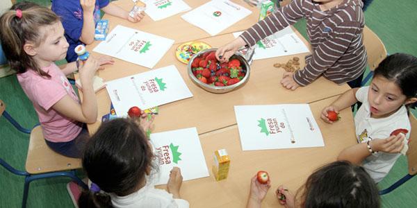 Niños de Moguer disfrutando las fresas de Cuna de Platero.